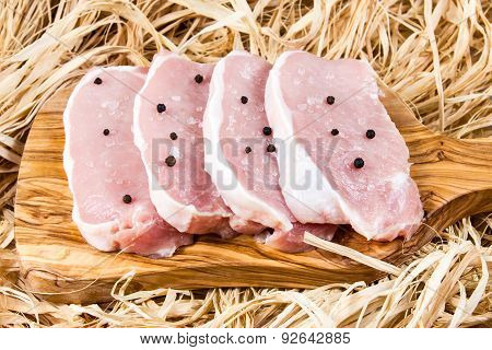 Boneless Pork Loin Steaks on cutting board and straw, with pepper