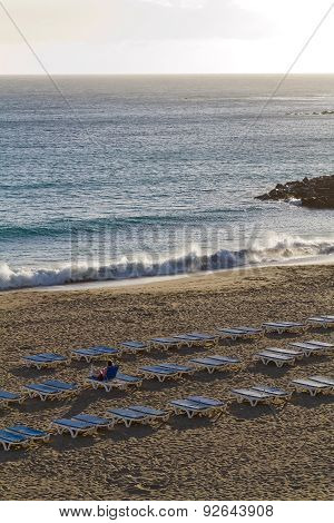 A Woman Lying Down On A Beach Chair On The Coast With All Empty Beach Chairs Placed Up On The Beach