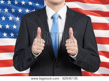 A Person In A Suit Thumbs Up. United States Flag As A Background.