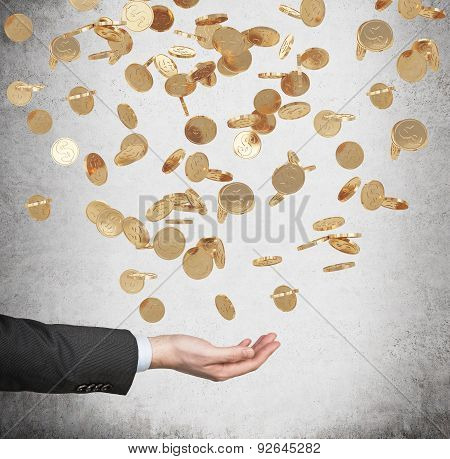 Close Up Of The Open Palm And Falling Golden Dollar Coins From The Ceiling. Concrete Background.