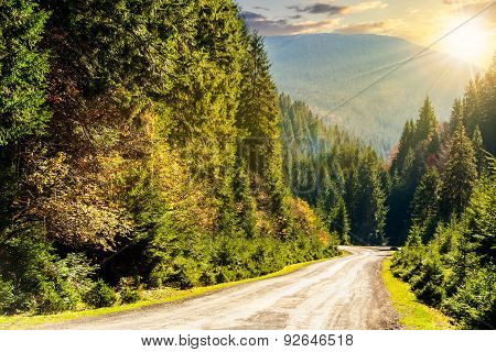 Road Through The Forest In Mountains At Sunset