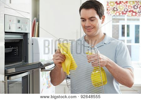 Man Cleaning Domestic Oven In Kitchen