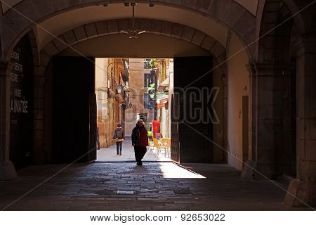 BARCELONA, SPAIN- MAR 16 2015 : Pedestrians stroll a side street in the Gothic Quarter.