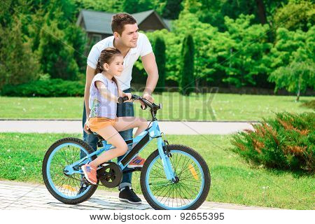 Father teaching daughter to ride a bike
