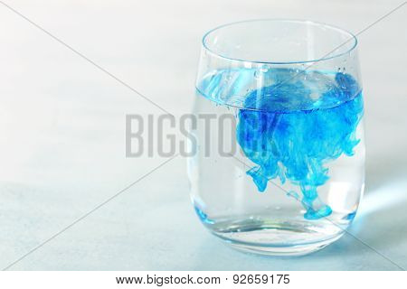 Glass of water with blue paint on table close up