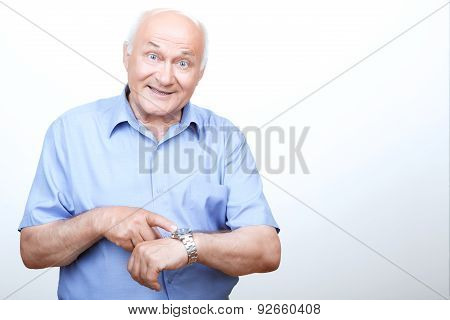 Vivacious grandfather pointing his wristwatch