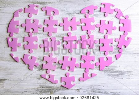 Pink puzzle heart on wooden background