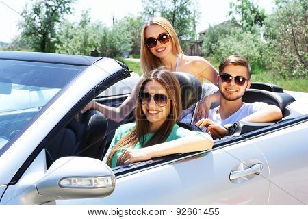 Three friends in cabriolet, outdoors