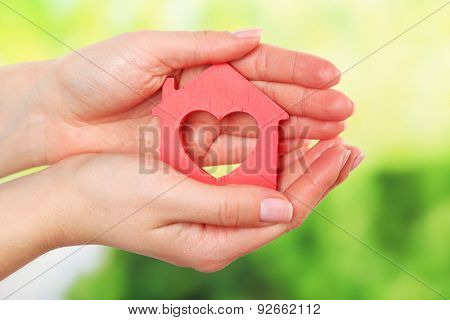 Female hands holding model of house on bright background