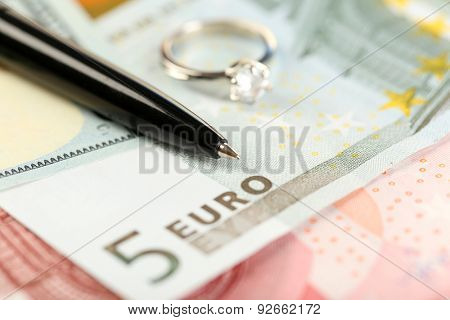 Wedding ring and pen on banknotes background. Marriage of convenience