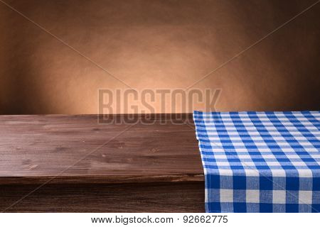 Empty wooden table with napkin and brown background