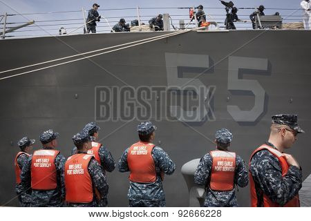 STATEN ISLAND, NY - MAY 20 2015: Sailors from NWS Earle Port Services wait to tend the lines of the guided-missile destroyer USS Stout (DDG 55) as the ship docks at Sullivans Pier for Fleet Week NY.