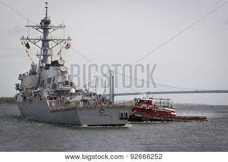 STATEN ISLAND, NY - MAY 20, 2015: USS Barry (DDG 52) is guided into port near the Verrazano-Narrows Bridge by McAllister tugboats at Sullivans Pier after the Parade of Ships that starts Fleet Week.