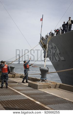 STATEN ISLAND, NY - MAY 20 2015:  A sailor from NWS Earle Port Services throws a line to personnel of guided-missile destroyer USS Barry (DDG 52) as the ship docks at Sullivans Pier for Fleet Week NY.