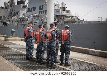 STATEN ISLAND, NY - MAY 20 2015: Sailors from NWS Earle Port Services wait to tend the lines of the guided-missile destroyer USS Barry (DDG 52)  as the ship docks at Sullivans Pier for Fleet Week NY.