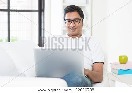 Indian guy listening to music with headset and laptop computer at home. Asian man using internet indoor, relaxed and sitting on sofa. Handsome male model.