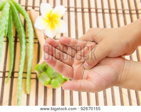 Hand Pain With Blurred Aloe Vera And Frangipani Flower Background