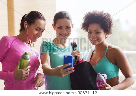 fitness, sport, training, gym and lifestyle concept - group of happy women with bottles and smartphone in gym