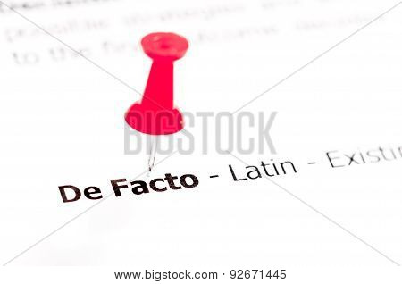 Words De Facto Pinned On White Paper With Red Pushpin