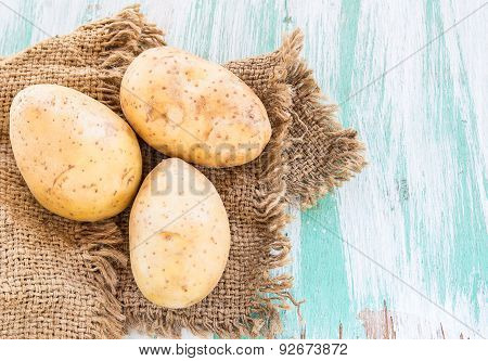 Sack Fresh Organic Potatoes On A Wooden Table