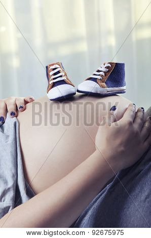 Small Shoes For The Unborn Baby On The Belly Of Pregnant Woman