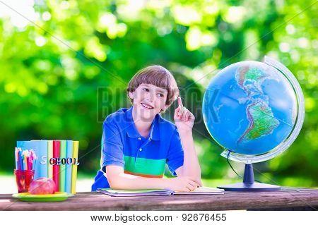 School Boy Doing Homework In School Yard