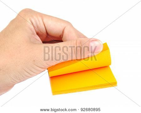 Hand with a block of yellow post it notes or notepapers on a white background