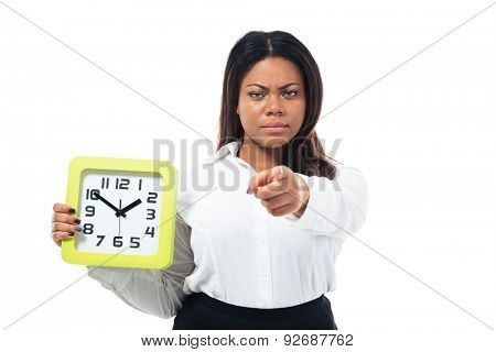 Angry afro american businesswoman holding clock and pointing finger at camera. Isolated on a white background