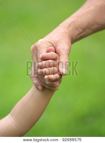 Child and grandma holding hands closeup