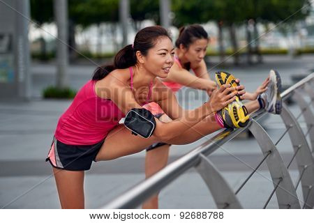 athletic asian chinese women doing stretching exercises outdoors along city sidewalk