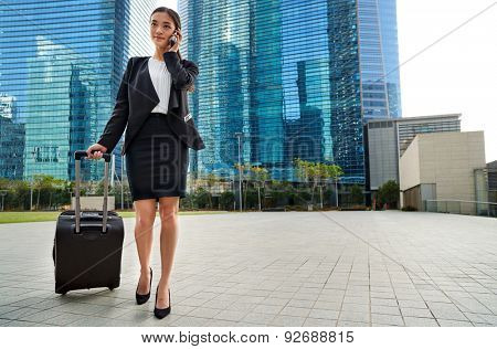 professional asian chinese travel business woman pulling suitcase bag walking along sidewalk on mobile phone outdoors in urban city