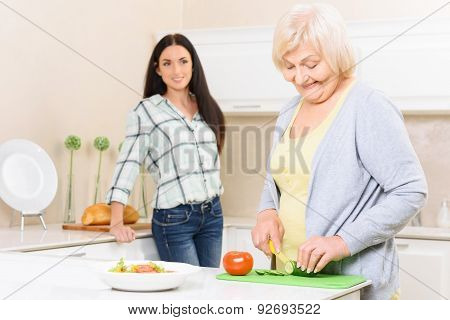 Granny cutting vegetables in kitchen