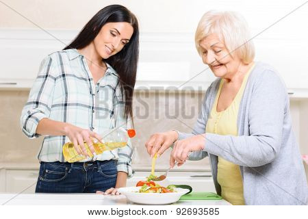 Grandmother and granddaughter making salad