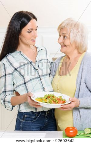 Pair of women holding salad in kitchen
