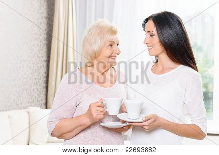 Granddaughter and grandmother standing with cups
