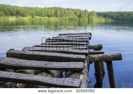 clear forest lake landscape and wooden footbridge