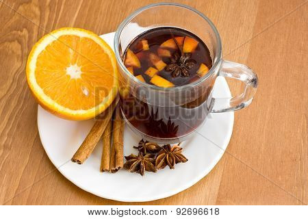 Christmas hot wine with oranges on wooden table