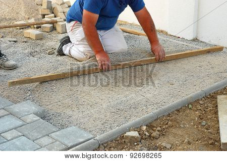 Construction site worker  leveling the sand during installing concrete brick pavement