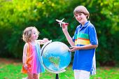 picture of girl toy  - Two happy children cute curly toddler girl and a smiling school age boy play with toy airplanes flying over the globe dreaming of traveling around the world - JPG