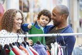 foto of mall  - Family Looking At Clothes On Rail In Shopping Mall - JPG