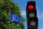 picture of traffic light  - EU flag near red traffic light under blue sky - JPG