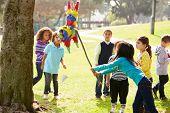 image of pinata  - Children Hitting Pinata At Birthday Party - JPG