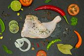 stock photo of thighs  - The chicken thigh and spices on black stone backgrund for decorate project - JPG