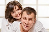 pic of laying-in-bed  - Happy smiling couple laying laughing in bed with light window background - JPG