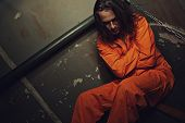 foto of lockups  - Miserable prisoner in orange clothes sitting on a bed in his cell - JPG