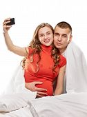 pic of two women taking cell phone  - A pregnant woman and her husband are photographing themselves on the cell phone on white back - JPG