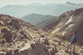 stock photo of rocky-mountains  - Hiker standing on steep rocky mountain footpath and looking at the wide panorama - JPG