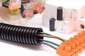 picture of fuse-box  - Corrugated plastic pipe cable with connection block and electric fuse copper wire connections components for use in electrical installations energy concept - JPG