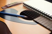 stock photo of risque  - Notebook and pencil on guitar Writing music - JPG