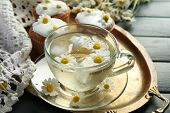 picture of chamomile  - Cup of chamomile tea with chamomile flowers and tasty muffins on tray - JPG